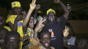 Supporters of Guinea president Alpha Conde gather in a street to celebrate his election victory. (AP)