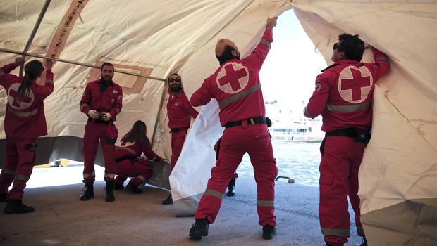 Greek Red Cross volunteers set up a tent which will be used to receive and offer initial care to hundreds of immigrants on a crippled freighter (AP)