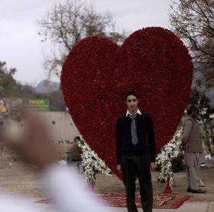 A Pakistani youth poses for a picture taken by his friend in front of a big red heart made of flowers displayed outside flowers shop on Valentine's Day, in Islamabad (AP)