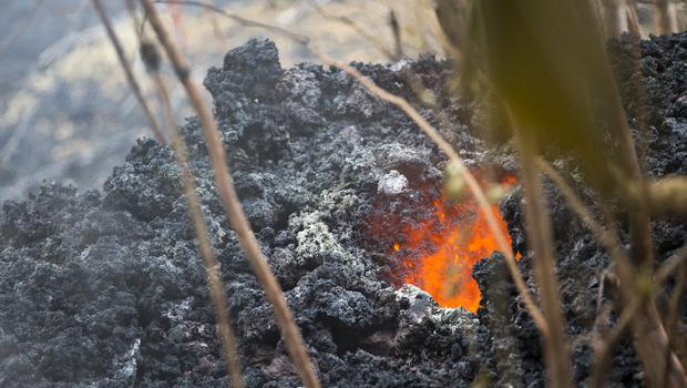 Lava glows from a vent on a lava bed at the Leilani Estates (Marco Garcia/AP)