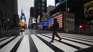 A man crosses the street in a nearly empty Times Square. As New York braces for a coronavirus disaster, the US Senate passed a massive 2.2 trillion dollar economic rescue package (Mark Lennihan/AP)
