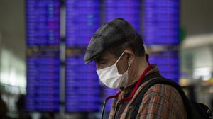 A man looks at his phone in front of the information screen at Barcelona airport in Spain (Emilio Morenatti/AP)