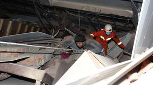 A man is assisted out from the rubble of a collapsed hotel building in Quanzhou city (Chinatopix/AP)
