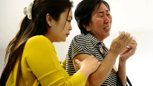 Relatives of missing Air Asia QZ8501 passengers cry at the crisis centre in Indonesia