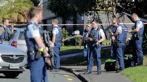 Armed police gather at the scene of a shooting (Michael Craig/New Zealand Herald/AP)