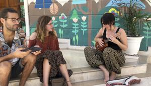 Briton Emma Snashford listens as another stranded tourist plays a ukulele in New Delhi (Shonal Ganguly/AP)