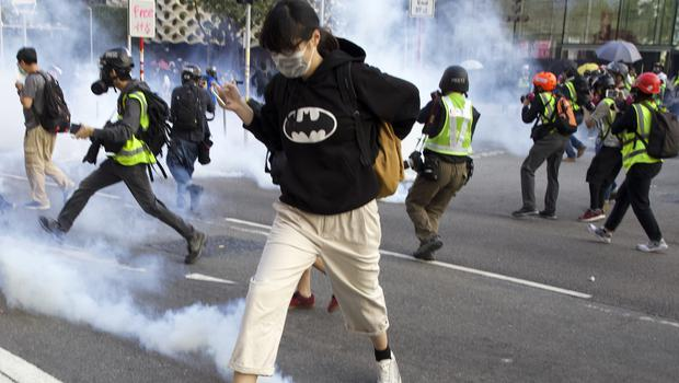 A pro-democracy protester runs away from the tear gas fired by riot police during a rally in Hong Kong (Ng Han Guan/AP)