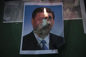 A candle burns on a photo of Chinese President Xi Jinping (Kin Cheung/AP)
