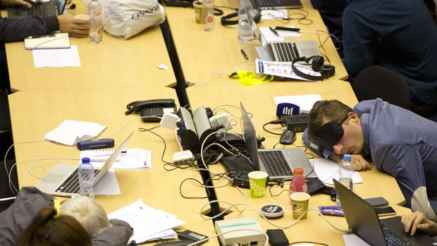 Journalists rest during a late-night negotiating session at an EU summit in Brussels (Virginia Mayo/AP)