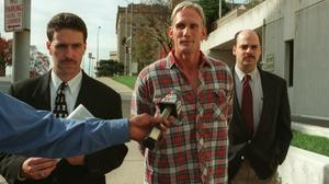 Wesley Ira Purkey (centre) is escorted by police officers in Kansas City after his arrest in 1998 (Jim Barcus/The Kansas City Star/AP)