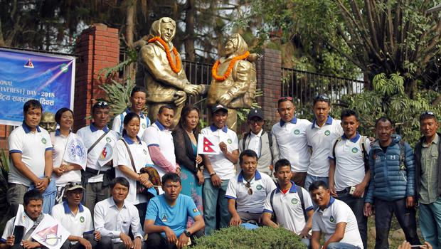 Nepalese mountain climbers pose in front of the statues of New Zealander Edmund Hillary and his Sherpa guide Tenzing Norgay during a function organised to mark Everest Day in Kathmandu (Niranjan Shrestha/AP)