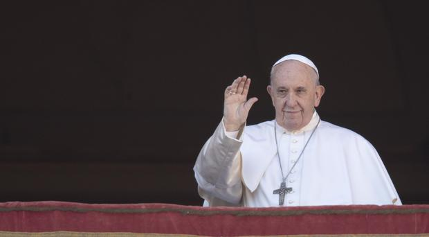 Pope Francis waves to faithful as he arrives to deliver the Urbi et Orbi Christmas Day blessing from the main balcony of St Peter's Basilica at the Vatican (Alessandra Tarantino/AP)