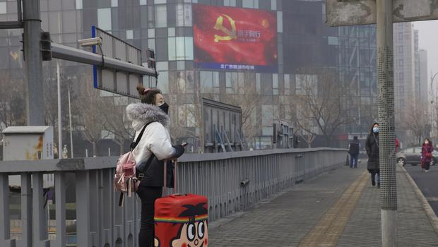A traveller stands on a bridge near a display showing government propaganda in the fight against the COVID-19 viral illness (Ng Han Guan/AP)