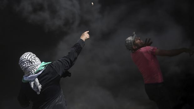 Palestinian protesters hurl stones at Israeli troops during a protest at the Gaza Strip's border with Israel (AP)