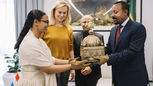 Ethiopia's Prime Minister Abiy Ahmed, right, receives a crown returned from the Netherlands (The Office of Prime Minister Abiy Ahmed via AP)