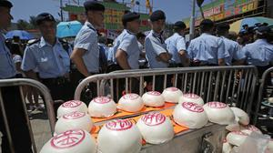 Police officers guard the buns for sale on the outlying Cheung Chau island in Hong Kong (Kin Cheung/AP)