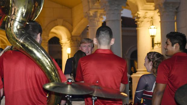 Donald Trump talks with members of the Florida Atlantic University Marching Band after they performed during a Super Bowl party at the Trump International Golf Club in West Palm Beach, Florida