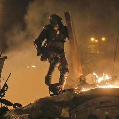 An anti-government protester runs during clashes with riot police in Kiev's Independence Square (AP)