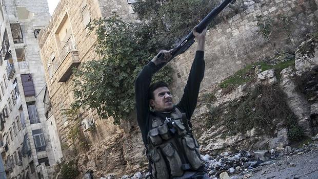 A Syrian rebel fighter aims at Syrian government forces during skirmishes in Aleppo (AP)