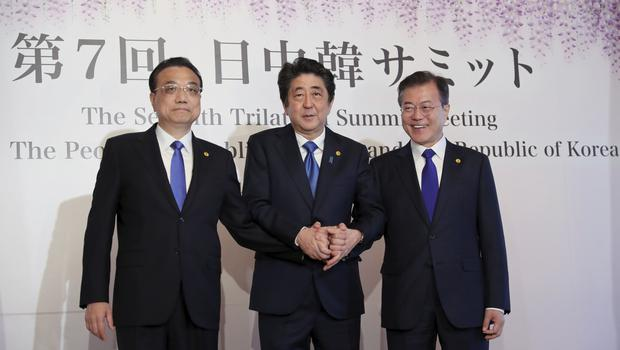 Chinese premier Li Keqiang, left, Japanese prime minister Shinzo Abe, centre, and South Korean president Moon Jae-in, right, prior to their summit in Tokyo (Eugene Hoshiko/AP)