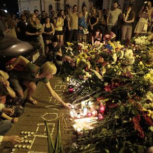 People hold candles and lay flowers outside the Dutch embassy in Kiev to commemorate victims of the Malaysia Airlines plane crash (AP)