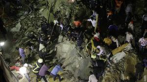 Rescue workers and civilians search for survivors in the rubble of a building that collapsed in Cairo (AP)