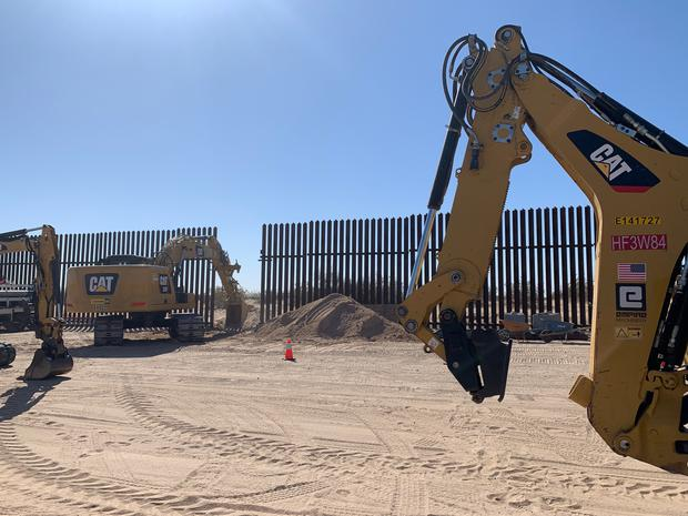Workers mending the fence on Wednesday (Eugene Garcia/AP)