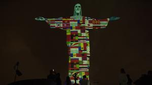 Rio's Christ the Redeemer statue is lit up with the flags of coronavirus-afflicted countries (Silvia Izquierdo/AP)