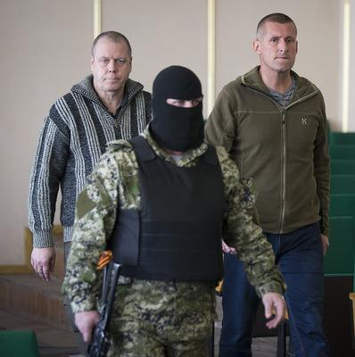 John Christensen, right, a senior sergeant in the Danish army, and his colleague, both members of the foreign military observers group, are escorted by a pro-Russian militant to the Slovyansk press conference (AP)