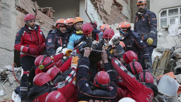 An injured man found in the rubble of a building destroyed in the quake in Elazig is carried to safety by rescue workers (Presidential Press Service via AP, Pool)