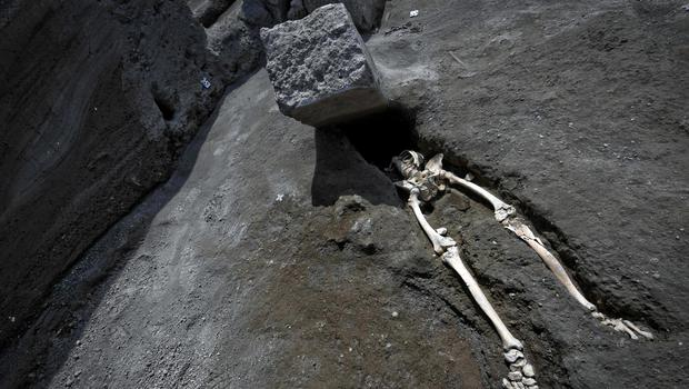 The legs of the skeleton emerge from the ground beneath a large rock (Ciro Fusco/ANSA/AP)