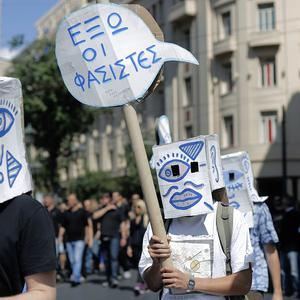 Demonstrators carry a placard which reads 'Fascists Out' during a protest in central Athens (AP/Petros Giannakouris)