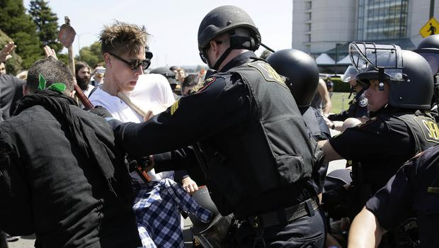 Police officers push back a group protesting against Republican presidential candidate Donald Trump outside of the Hyatt Regency hotel. (AP File Photo)