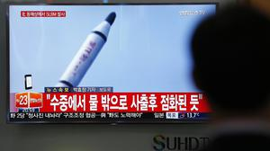 A man watches a TV news program showing a file footage of a missile launch conducted by North Korea (AP)