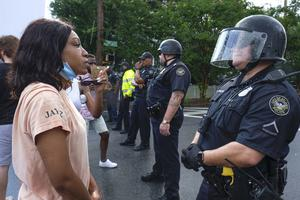 Protesters stand in front of police during demonstrations in Atlanta (Ben Gray/Atlanta Journal-Constitution via AP)