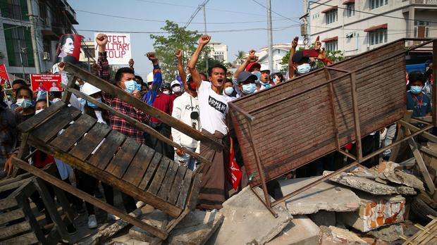 Protesters shout slogans as police arrive during a protest against the military coup in Mandalay, Myanmar (AP)