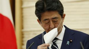 Japan's Prime Minister Shinzo Abe takes off his protective mask as he begins his news conference in Tokyo Monday, May 25, 2020. Abe lifted a coronavirus state of emergency in Tokyo and four other remaining areas on Monday, ending the restrictions nationwide. (Kim Kyung-hoon/Pool Photo via AP)