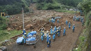 Rescuers search for missing people at the site of a mudslide caused by heavy rain in Natsugi town, Kumamoto prefecture, Japan (Kyodo/AP)