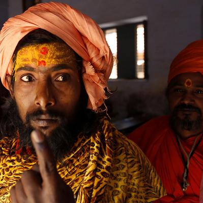 A Hindu holy man displays the ink mark on his finger after casting his vote, in Haridwar, India (AP)