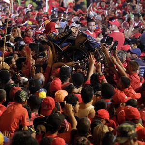A man in a wheelchair is carried over the crowd during the closing campaign rally for Venezuela's acting president Nicolas Maduro in Caracas (AP)