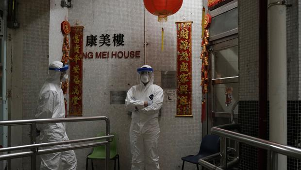 People wearing protective suits stand near an entrance at the Cheung Hong Estate (Kin Cheung/AP)