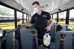 Des Moines Public Schools mechanic Kelly Silver cleans the interior of a school bus in Iowa (AP)