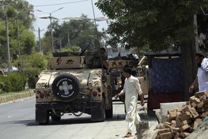 Afghan security personnel gather in front of the prison (Rahmat Gul/AP)