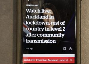 A news alert is displayed on a mobile phone in Christchurch, New Zealand (AP/Mark Baker)