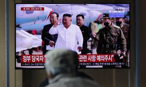 People watch a TV screen showing a news programme reporting about North Korean leader Kim Jong Un (Lee Jin-man/AP)