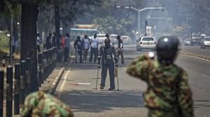 A pedestrian on crutches tries to flee as police fire tear gas grenades, at demonstration against police killings of protesters and opposition supporters in Nairobi (AP)