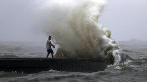 A wave crashes near Orleans Harbour in Lake Pontchartrain (Gerald Herbert/AP)