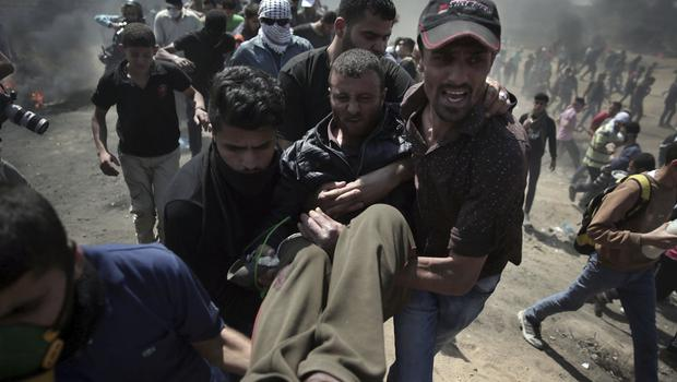 Palestinian protesters carry an injured man who was shot by Israeli troops (AP)