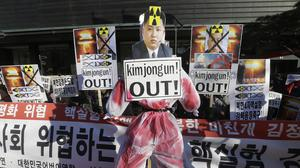 South Korean protesters bearing defaced photos of North Korean leader Kim Jong Un protest against the North's announcement that it had tested a hydrogen bomb (AP)