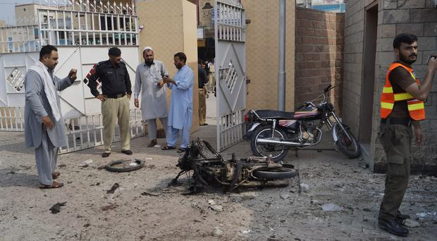 Pakistani security officials examine the site of a bombing (Ishtiaq Mahsud/AP)